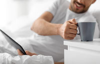 man with tablet computer drinking coffee in bed