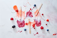 Bright pattern of splashes of ice cream of different fresh berries and sticks on a gray marble background background with copy space.