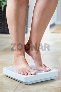 Woman Standing on Weight Scale At Home