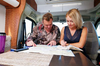 Middle aged married couple talking about future adventure planning route looking at map sitting inside of recreational vehicle motor home trailer. Active lifestyle