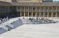 people relaxing on the steps and and walking across the square of halifax piece hall in west yorkshire
