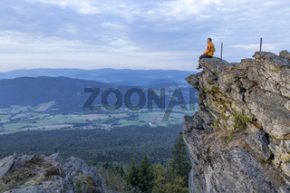 Man sit on a ledge in the Bavarian Forest.