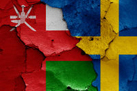 flags of Oman and Sweden painted on cracked wall
