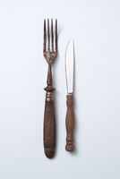 Old fork and knife with wooden handle isolated on gray background with copy space. Vintage tableware