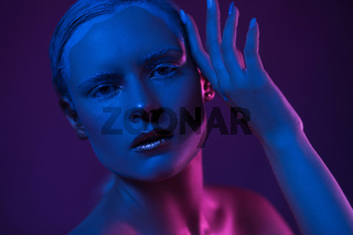 Young Pretty Woman with Cool Make Up. Neon Blue and Purple Lights on Face.