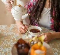 Pouring tea from porcelain teapot to the cup.