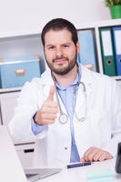 Bearded doctor working at his office showing thumbs up. Business and medical concept.