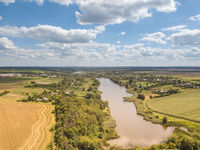 Panoramic view with farmfields, countries, wide river on a background blue cloudy sky in a summer day.