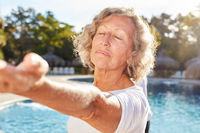 Senior Frau macht Yoga Meditation am Pool