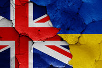 flags of UK and Ukraine painted on cracked wall