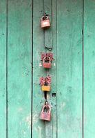 Wooden door locked by 4 different padlocks