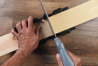 High angle closeup of a woodworker using a miter box and hand saw to cut a board