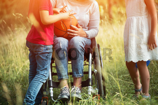 Young woman's legs in wheelchair with children aroud her