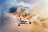 Airplane flying above mountains and low clouds at sunset