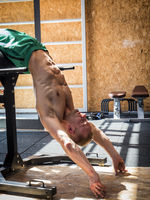 Handsome young man exercising abs with gym equipment