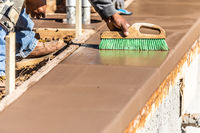 Construction Worker Using Brush On Wet Cement Forming Coping Around New Pool