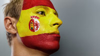 Emotional football fan with spain flag painted on his face over gray background