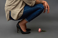 Composition from pink flower and stylish girl squatting against a dark background with copy space for text. As a mock-up for a greeting card