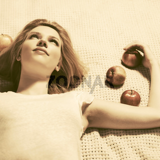 Happy young woman with apples lying on the plaid outdoor