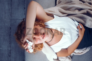 Elevated view on sick woman laying with a hand on her forehead