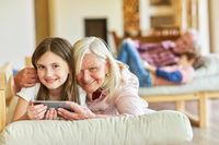 Glückliche Oma und Enkel Tochter mit Smartphone