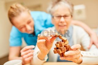 Senior Frau mit Demenz spielt mit Holzpuzzle