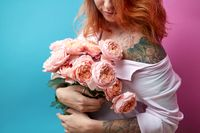 Attractive red-haired girl with tattoo on shoulders and hands holds a bunch of coral roses on a blue-pink background. A gift for Mother's Day.