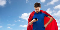 man in red superhero cape with smartphone over sky