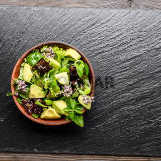 Top view at clay dish with salad of avocado, green and violet lettuce, lamb's lettuce and oregano flowers on slate stone tray