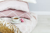 Pink and white pillows and cup of coffee on the wall background