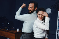 Business people showing muscles in office