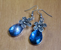 Beautiful earrings with large blue stones on a wooden table (standard mass production).