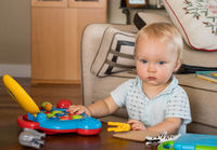 Infant caucasian boy working on toy computer on table