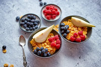 Golden cornflakes with fresh fruits of raspberries, blueberries and pear in ceramic bowl