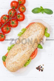 Sandwich Baguette Vollkorn Brötchen belegt mit Schinken Hochformat von oben auf Holzbrett
