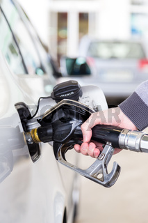 Closeup of mans hand pumping gasoline fuel in car at gas station.
