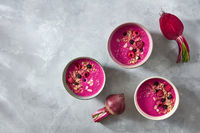 Red smoothies with berries and oatmeal on a concrete background with halves of a young beetroot, flat lay