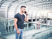 Young man in train station calling on cellphone