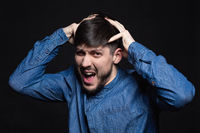 Attractive man screaming posing in studio