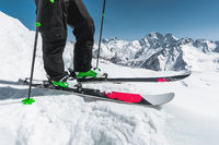 A close-up of the ski on the athlete's feet against the background of snow-capped rocky mountains. The concept of winter sports in the mountains