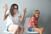 Happy mother and her little daughter sitting on the chairs. Portrait of mother and daughter with eyeglasses