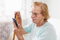 Elderly woman with glasses and cane using a mobile phone