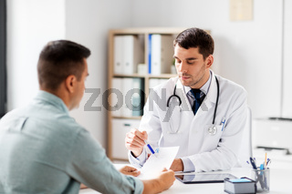 doctor showing prescription to patient at hospital