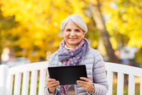 senior woman with tablet pc at summer park