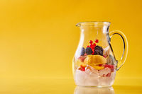 Glass jug with citrus, berries and ice on a yellow background.