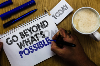 Text sign showing Go Beyond What s is Possible. Conceptual photo do bigger things You can reach dreams Man holding marker notebook clothespin reminder wooden table cup coffee.