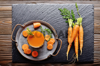 Top view at vegetarian background of old tray with carrots and juice on slate stone
