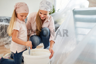 Kind hilft Mutter beim Malern und Renovieren