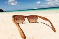 wooden sunglasses lying on the beach
