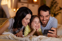 happy family with smartphone in bed at night